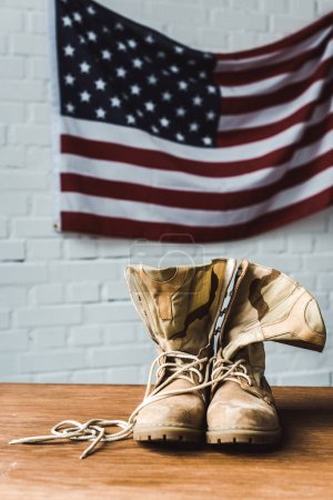 Photo for Military boots near american flag with stars and stripes on brick wall - Royalty Free Image