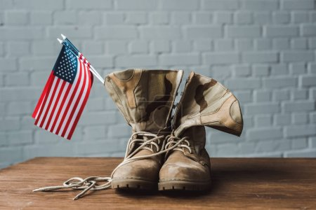 Photo for Military boots and american flags with stars and stripes on wooden surface - Royalty Free Image