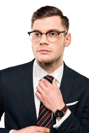 Foto de Handsome businessman in glasses touching tie isolated on white - Imagen libre de derechos