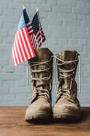 military boots and american flags with stars and stripes on wooden table