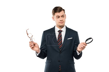 Foto de Handsome businessman holding glasses and magnifying glass isolated on white - Imagen libre de derechos