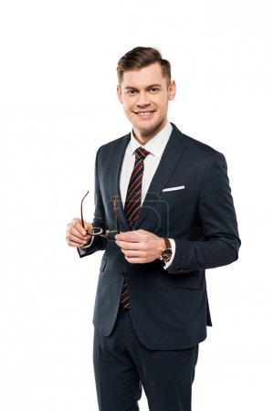 Photo for Smiling businessman holding glasses and looking at camera isolated on white - Royalty Free Image