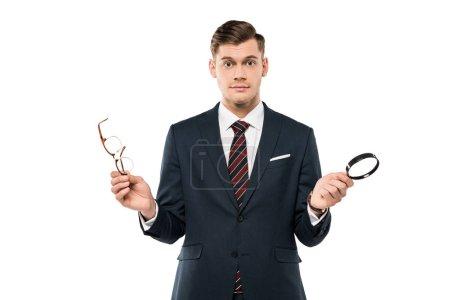 Foto de Empresario sorprendido sosteniendo gafas y lupa aislada en blanco - Imagen libre de derechos