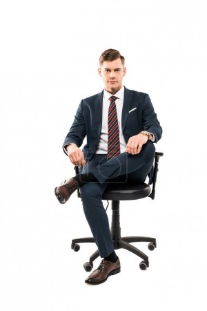 confident businessman sitting on chair and looking at camera isolated on white