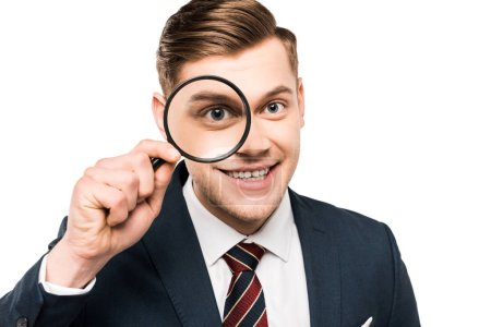 Foto de Cheerful businessman holding magnifying glass near eye isolated on white - Imagen libre de derechos