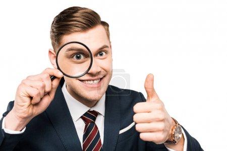 Foto de Alegre hombre de negocios mostrando el pulgar hacia arriba y sosteniendo la lupa cerca del ojo aislado en blanco - Imagen libre de derechos