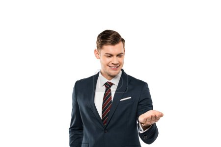 Photo for Cheerful businessman in suit looking at hand isolated on white - Royalty Free Image
