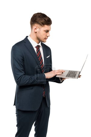 Foto de Handsome businessman using laptop while standing isolated on white - Imagen libre de derechos