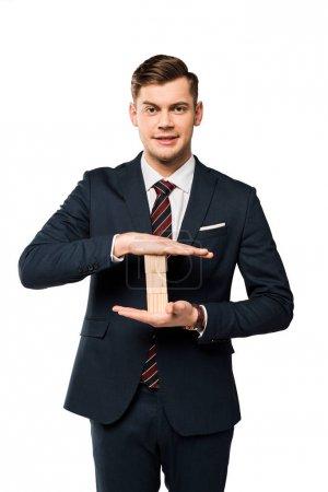 Photo pour Homme d'affaires gai dans le procès retenant des cubes en bois d'isolement sur le blanc - image libre de droit