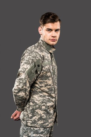 Foto de Handsome soldier looking at camera isolated on grey - Imagen libre de derechos
