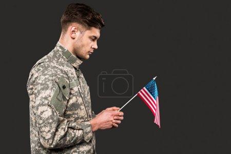 Photo pour Triste homme en uniforme militaire tenant drapeau américain isolé sur gris - image libre de droit