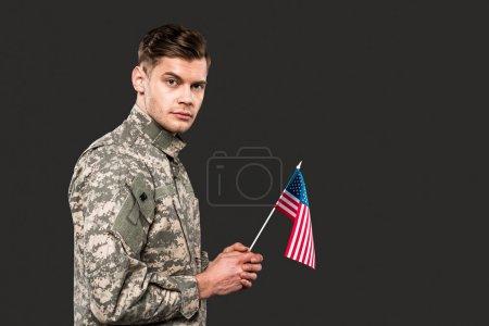 Photo pour Homme dans l'uniforme militaire retenant le drapeau américain d'isolement sur le gris - image libre de droit