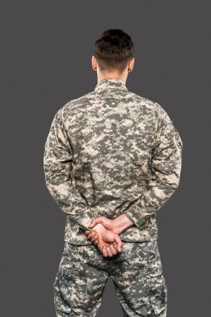 Photo for Back view of soldier standing with clenched hands isolated on grey - Royalty Free Image