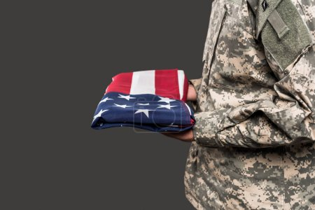 Photo for Cropped view of man in military uniform holding flag of america isolated on grey - Royalty Free Image