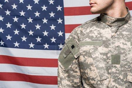 Photo pour Vue recadrée de l'homme en uniforme militaire près du drapeau de l'Amérique - image libre de droit