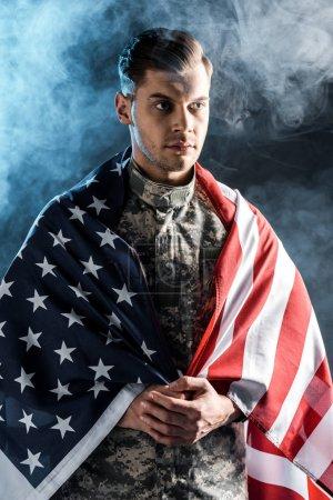 Photo pour Soldat dans l'uniforme militaire avec les mains serrées et le drapeau américain sur le noir avec la fumée - image libre de droit