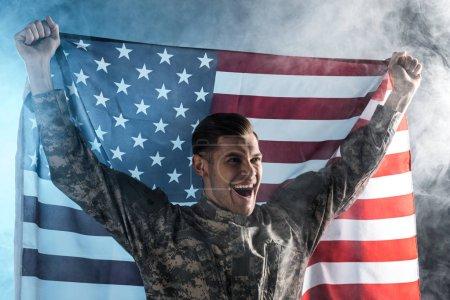Photo pour Soldat heureux geste tout en tenant drapeau américain sur noir avec de la fumée - image libre de droit