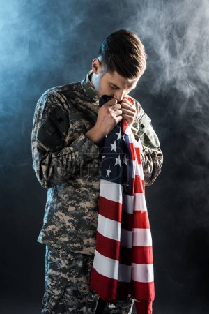 Photo for Handsome soldier with closed eyes smelling american flag on black with smoke - Royalty Free Image