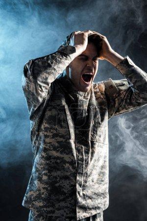 Photo pour Soldat émotif dans l'uniforme militaire criant sur le noir avec la fumée - image libre de droit