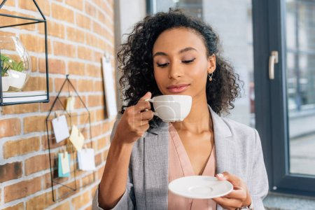 Photo for Beautiful african american Casual businesswoman with coffee cup in office - Royalty Free Image