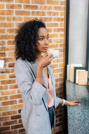 Photo for African american Casual businesswoman drinking coffee in office - Royalty Free Image