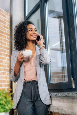 Photo pour Femme d'affaires américaine africaine occasionnelle avec la tasse de café parlant sur le smartphone dans le bureau de grenier - image libre de droit