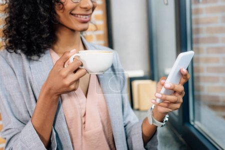 Photo for Cropped view of african american Casual businesswoman with coffee cup using smartphone - Royalty Free Image