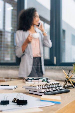 Foto de Enfoque selectivo de portátiles y gafas en el escritorio cerca de afroamericana Casual empresaria hablando en el teléfono inteligente - Imagen libre de derechos