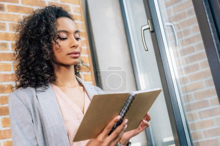 Photo for Beautiful african american Casual businesswoman holding notebook in loft office - Royalty Free Image