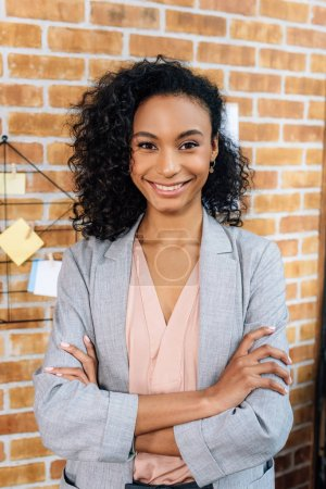 Photo for Smiling african american Casual businesswoman with crossed arms in loft office - Royalty Free Image