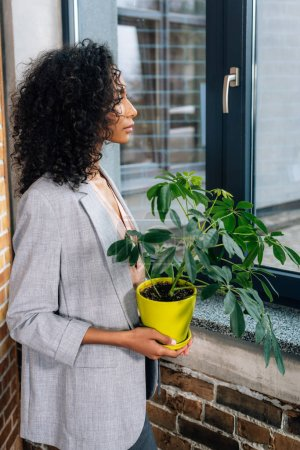african american Casual businesswoman holding flowerpot with plant in loft office