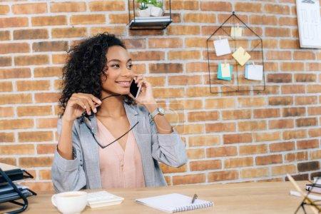Photo pour Femme d'affaires occasionnelle africaine de sourire parlant sur le smartphone au bureau - image libre de droit