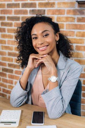 Photo pour Femme d'affaires occasionnelle africaine de sourire de support dans le bureau de grenier - image libre de droit
