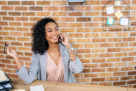 Photo for Smiling african american Casual businesswoman talking on smartphone at desk - Royalty Free Image