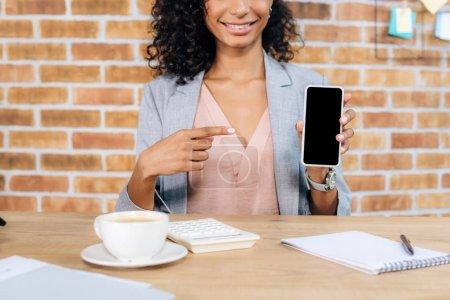 Photo pour Vue cultivée de femme d'affaires américaine africaine occasionnelle pointant avec le doigt au smartphone avec l'écran blanc dans le bureau de grenier - image libre de droit