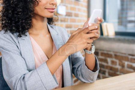 Photo pour Vue recadrée d'une femme d'affaires afro-américaine occasionnelle utilisant un smartphone dans un bureau loft - image libre de droit