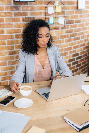 Foto de Afroamericano Mujer de negocios casual con taza de café usando computadora portátil en el escritorio de la oficina - Imagen libre de derechos