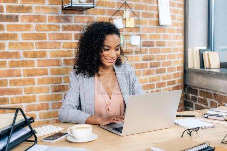 Photo pour Femme d'affaires occasionnelle africaine de sourire utilisant l'ordinateur portatif au bureau - image libre de droit