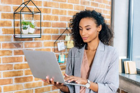 Photo for Beautiful african american Casual businesswoman using laptop in loft office - Royalty Free Image