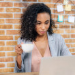 african american Casual businesswoman with coffee cup using laptop in office