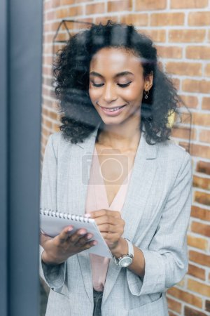 Photo for Beautiful smiling Casual businesswoman writing in notebook in loft office - Royalty Free Image
