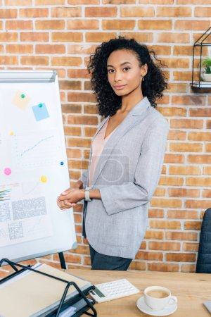 Photo for Beautiful african american Casual businesswoman near flipchart looking at camera in loft office - Royalty Free Image