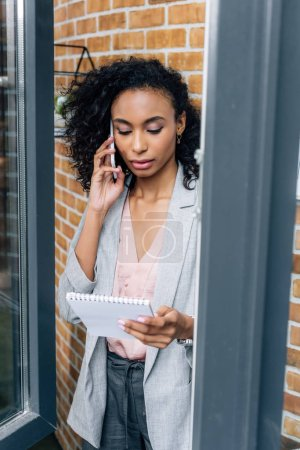 Photo for African american Casual businesswoman with notebook talking on smartphone - Royalty Free Image