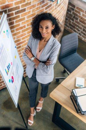 Photo pour Femme d'affaires occasionnelle africaine de sourire d'Amérique avec les bras croisés près de flipchart dans le bureau de grenier - image libre de droit