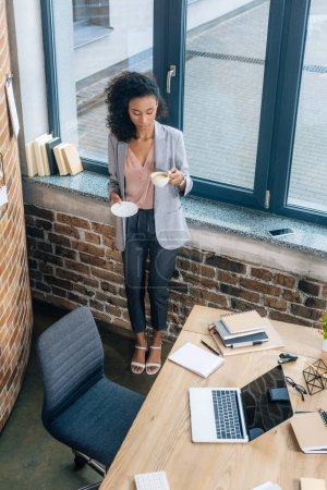 Photo for Beautiful african american Casual businesswoman with coffee cup near office desk with laptop - Royalty Free Image