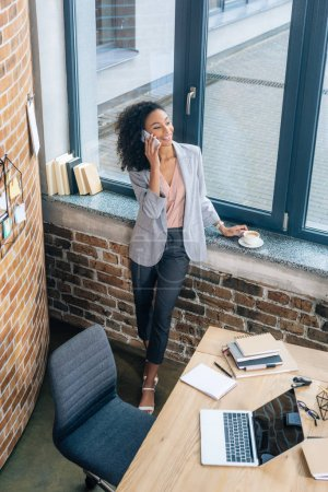 Photo for High Angle View of beautiful african american Casual businesswoman talking on smartphone in office - Royalty Free Image
