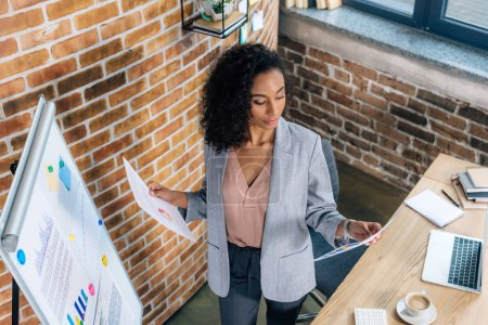 Photo pour African american Casual businesswoman holding papers near flipchart in loft office african american Casual businesswoman holding papers near flipchart in loft office - image libre de droit