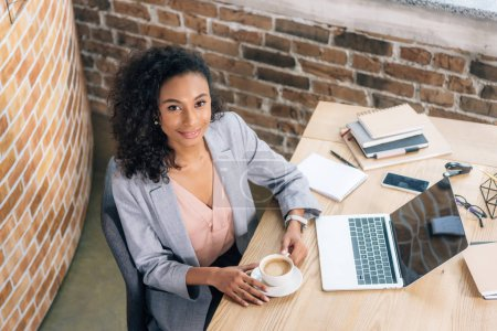 Photo for Smiling african american Casual businesswoman with coffee cup and laptop at desk in office - Royalty Free Image