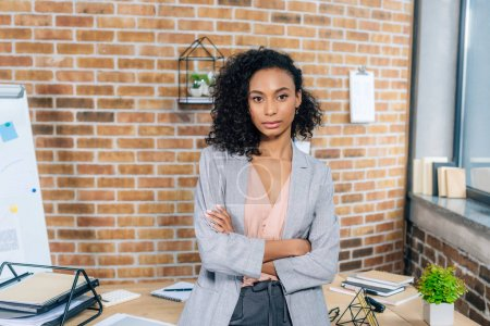 Photo for Confident african american Casual businesswoman with crossed arms in loft office - Royalty Free Image