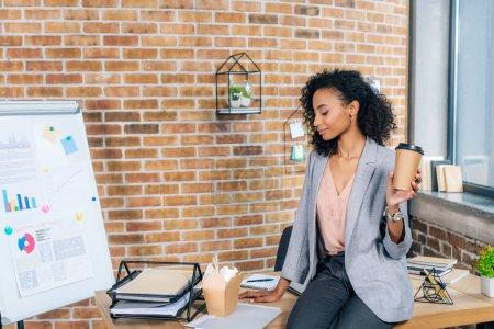 Photo pour Femme d'affaires afro-américaine occasionnelle s'asseyant sur le bureau avec le café pour aller et la boîte à emporter dans le bureau - image libre de droit